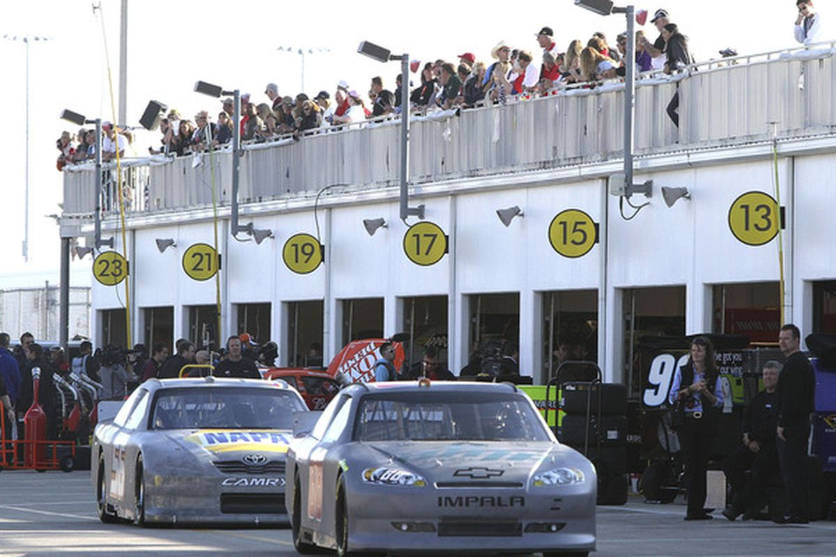 DAYTONA BEACH FL - JANUARY 20:  Race fans watch as cars go from the Sprint Fan Zone during testing at Daytona International Speedway on January 20 2011 in Daytona Beach Florida.  (Photo by Jerry Markland/Getty Images for NASCAR)