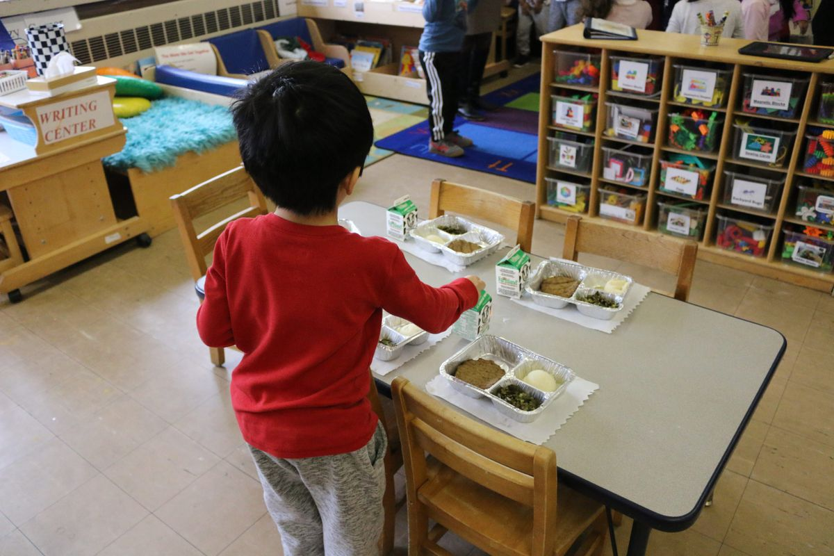 A pre-K student at HeartShare Taranto in Brooklyn helps prepare the classroom for lunch.