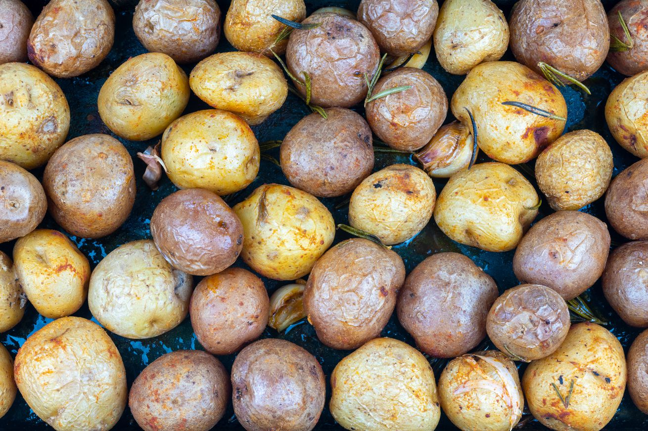 Small baked potatoes of two colors forming a food pattern.