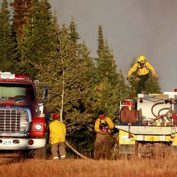 Firefighters refill their brush truck from a water tender while battling a wildfire Sunday, Sept. 9, 2012 on Casper Mountain in Casper, Wyo. Residences and campgrounds were evacuated as the uncontained wildfire spread across the southeast portion of the mountain.