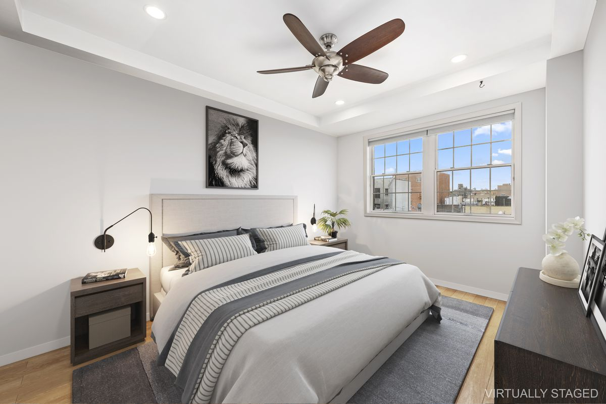 A bedroom with a large window, a large bed, and hardwood floors.