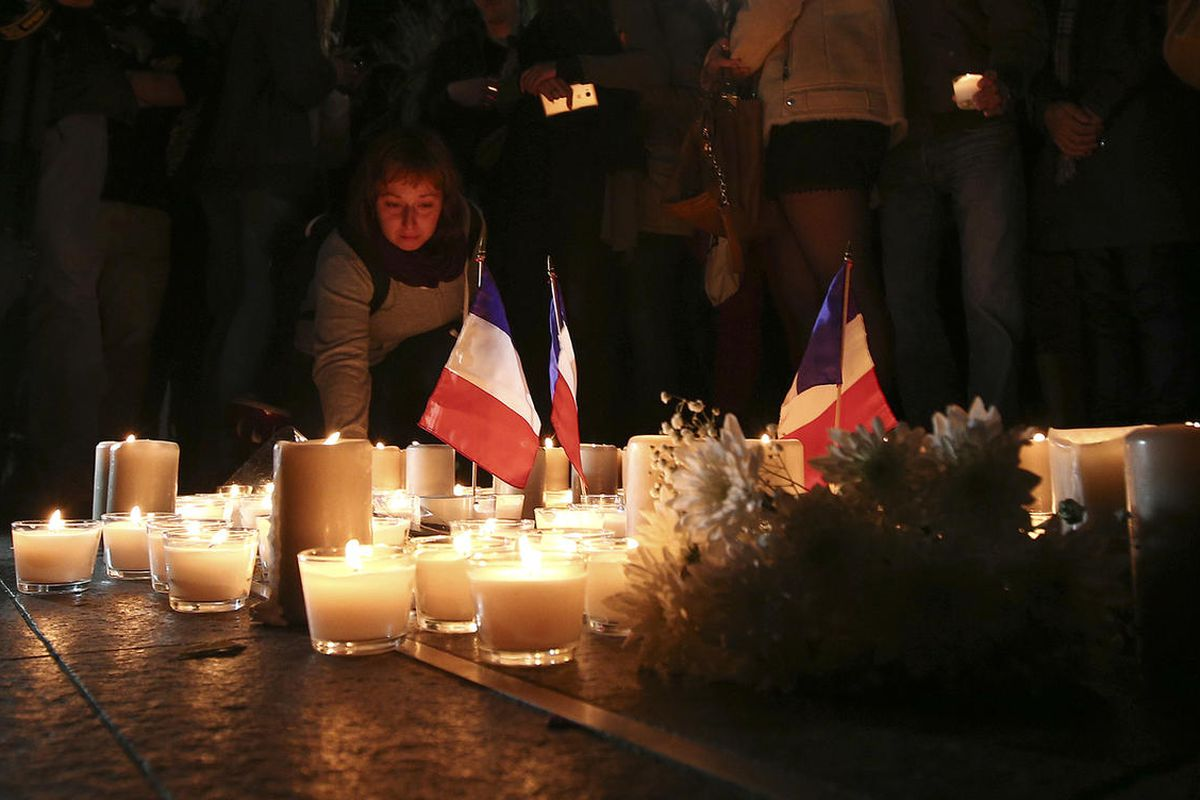 A woman places a candle during a vigil to honor victims of the Bastille Day tragedy in Nice, France, in Sydney, Australia, Friday, July 15, 2016. World leaders are expressing dismay, sadness and solidarity with France over the attack carried out by a man