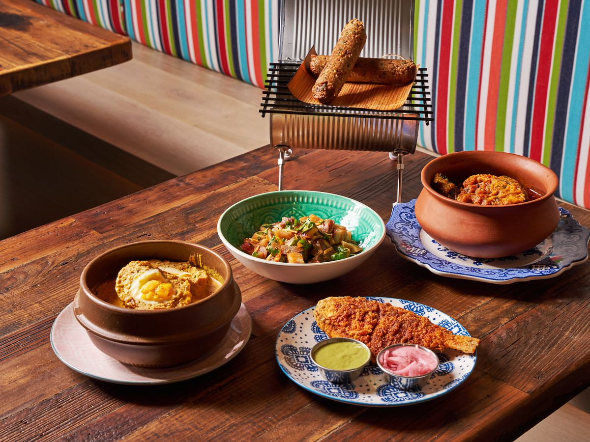 Several dishes of food lined up on a wooden table with a colorful bench in the background