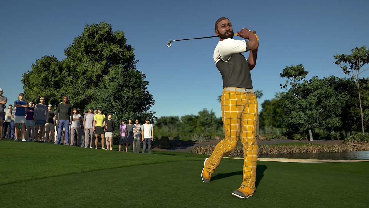 A golfer in a sweater vest and khakis whacks an approach shot from the fairway, as the gallery looks on, in PGA Tour 2K21