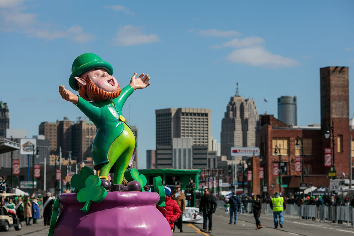 A parade float with a leprechaun holding his arms wide on a pink pot of gold at the Detroit St. Patrick's Day Parade.