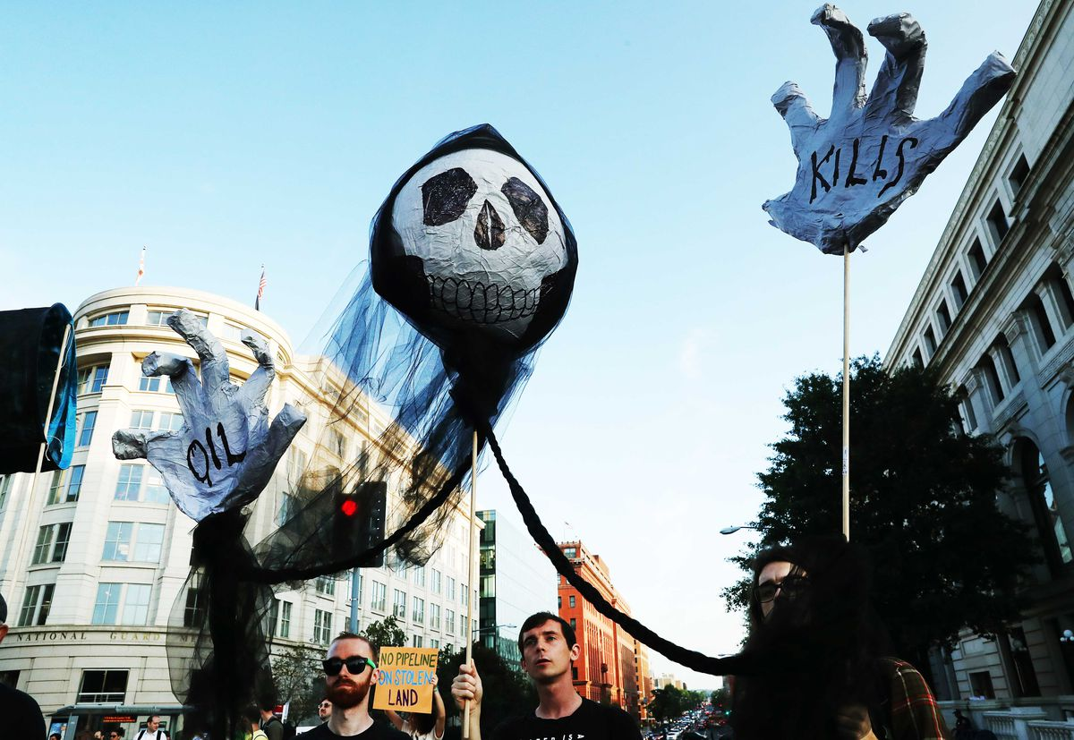 "Climate protesters seeking to block traffic on Massachusetts Avenue in Washington, DC, hold up a puppet skull with hands that read ""Oil kills."""
