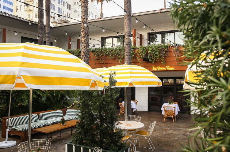 Yellow sun umbrellas and off-white tables and chairs at a poolside lounge in Hollywood.