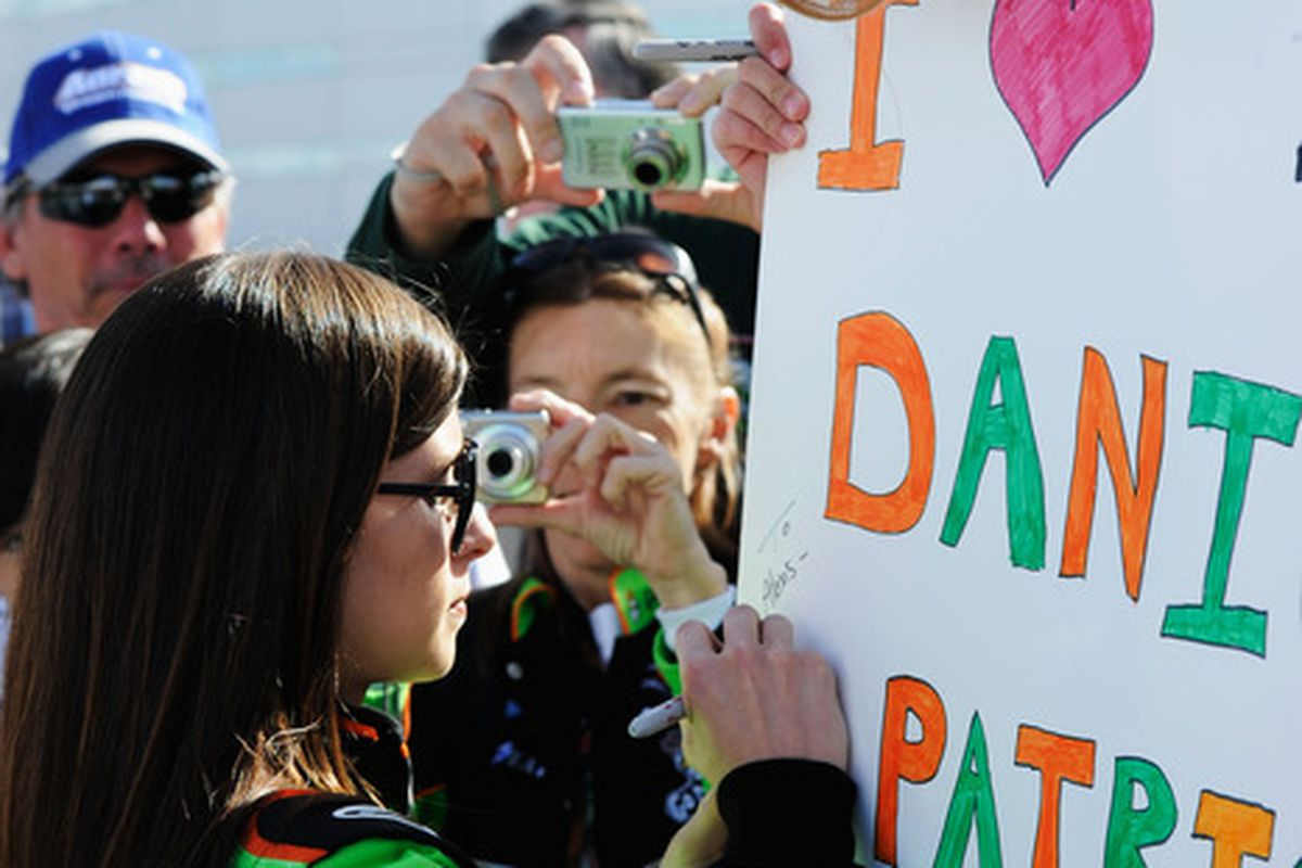 Danica Patrick signs a fan's poster during qualifying for the NASCAR Nationwide Series Sam's Town 300 at Las Vegas Motor Speedway.