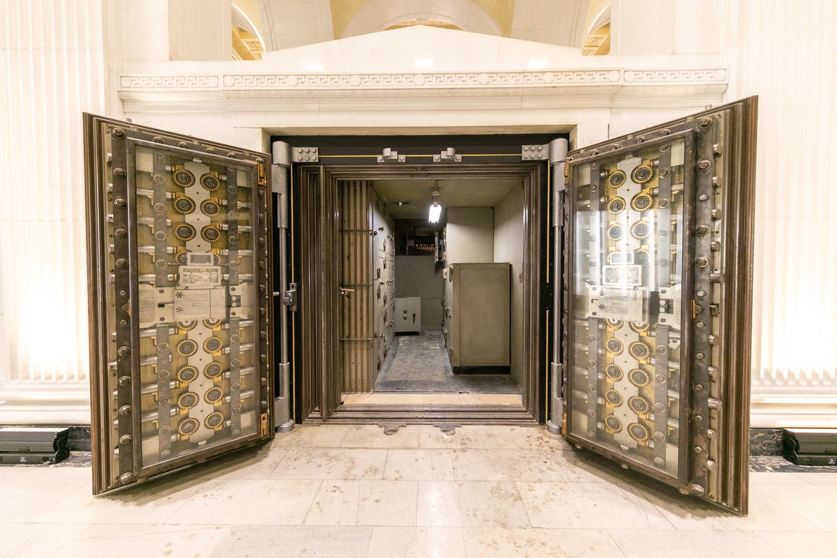 Two huge metal doors are opened with dozens of gears enclosed by glass. Inside the vault, there's more safes.