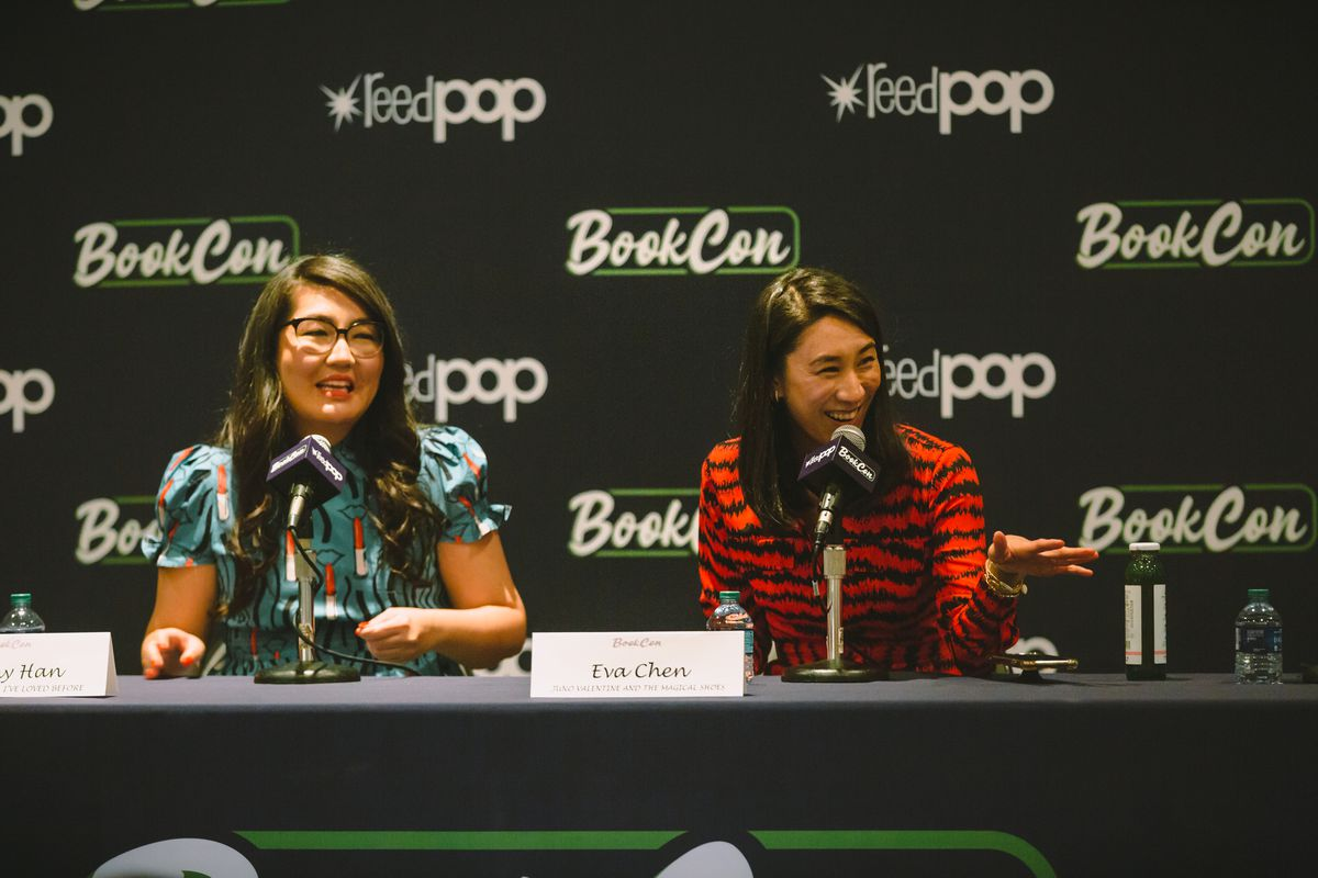 Jenny Han and Eva Chen sit talking at a table with microphones in front of them