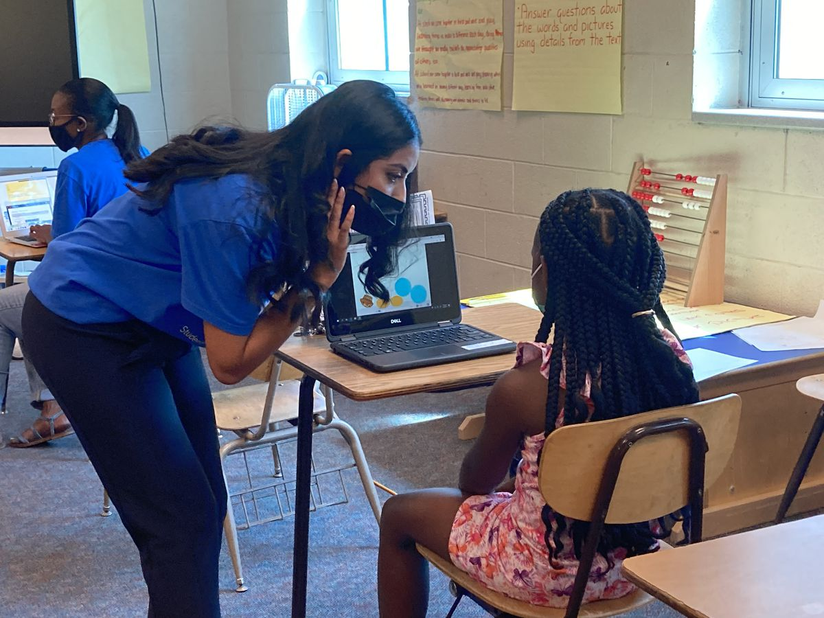A teacher leans over to help a student with a summer school exercise at Brenda Scott Academy in the Detroit school district.