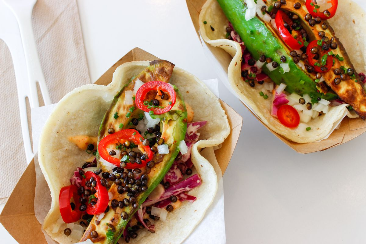 An overhead view of tacos stuffed with seared avocados, lentils, and other vegan ingredients