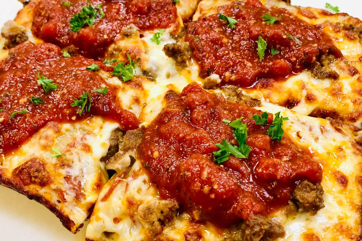 a Detroit-style square pizza with toasty cheese and big globs of tomato sauce