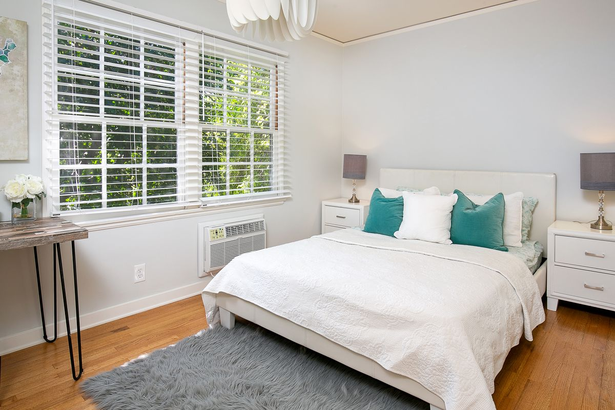 A spacious bedroom with two large windows on one wall.