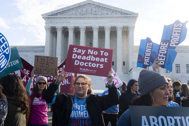 Protesters on both sides of the abortion issue hold signs in front of the Supreme Court.