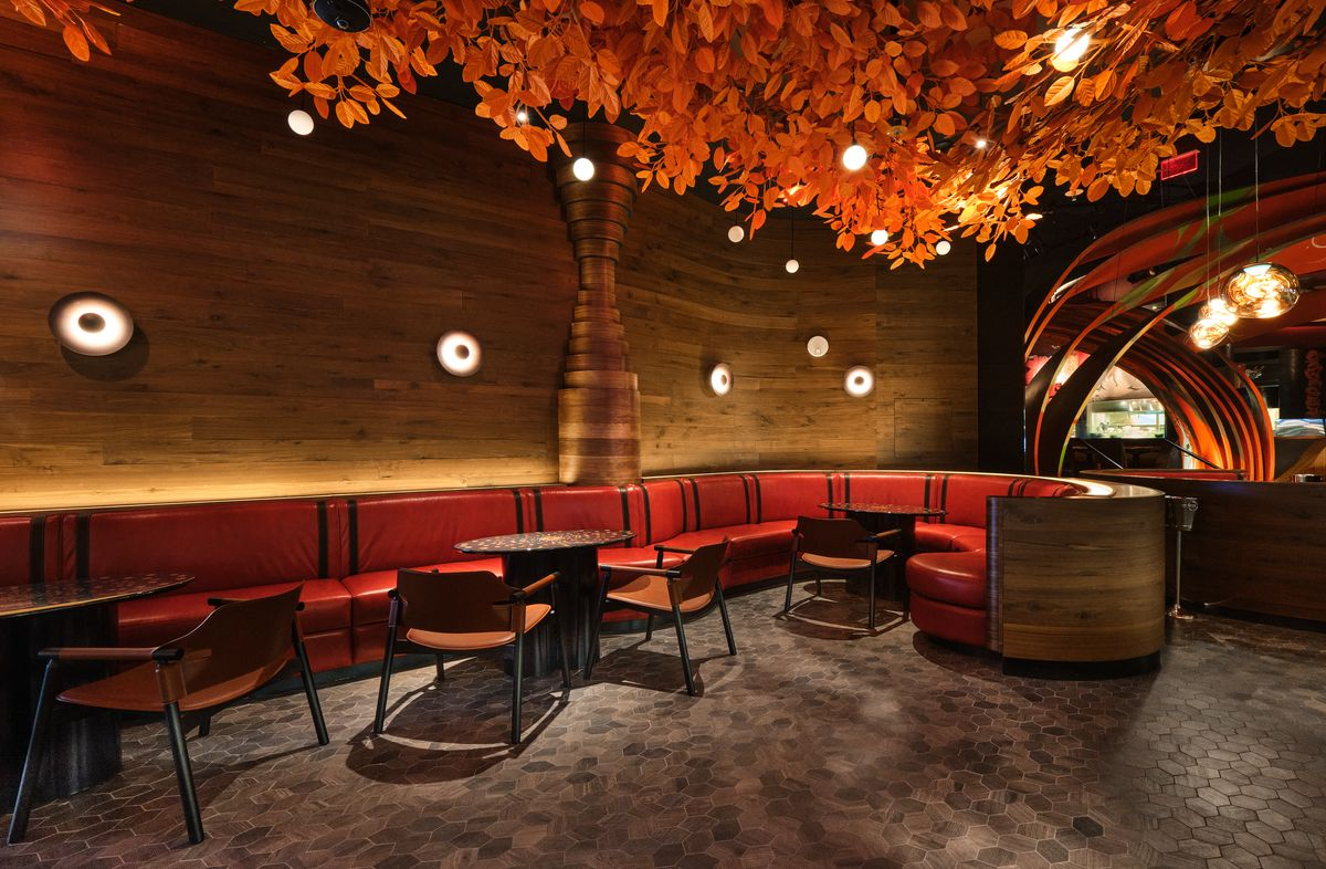 A lounge area with leather booths and orange leaves on a tree