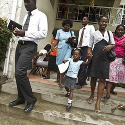 Members of the Petionville Ward leave after meetings at the Petionville LDS Meetinghouse in Petionville, Haiti, on Sunday. More than 600 people lived on the grounds in front of the church after the January earthquake that ravaged Haiti.