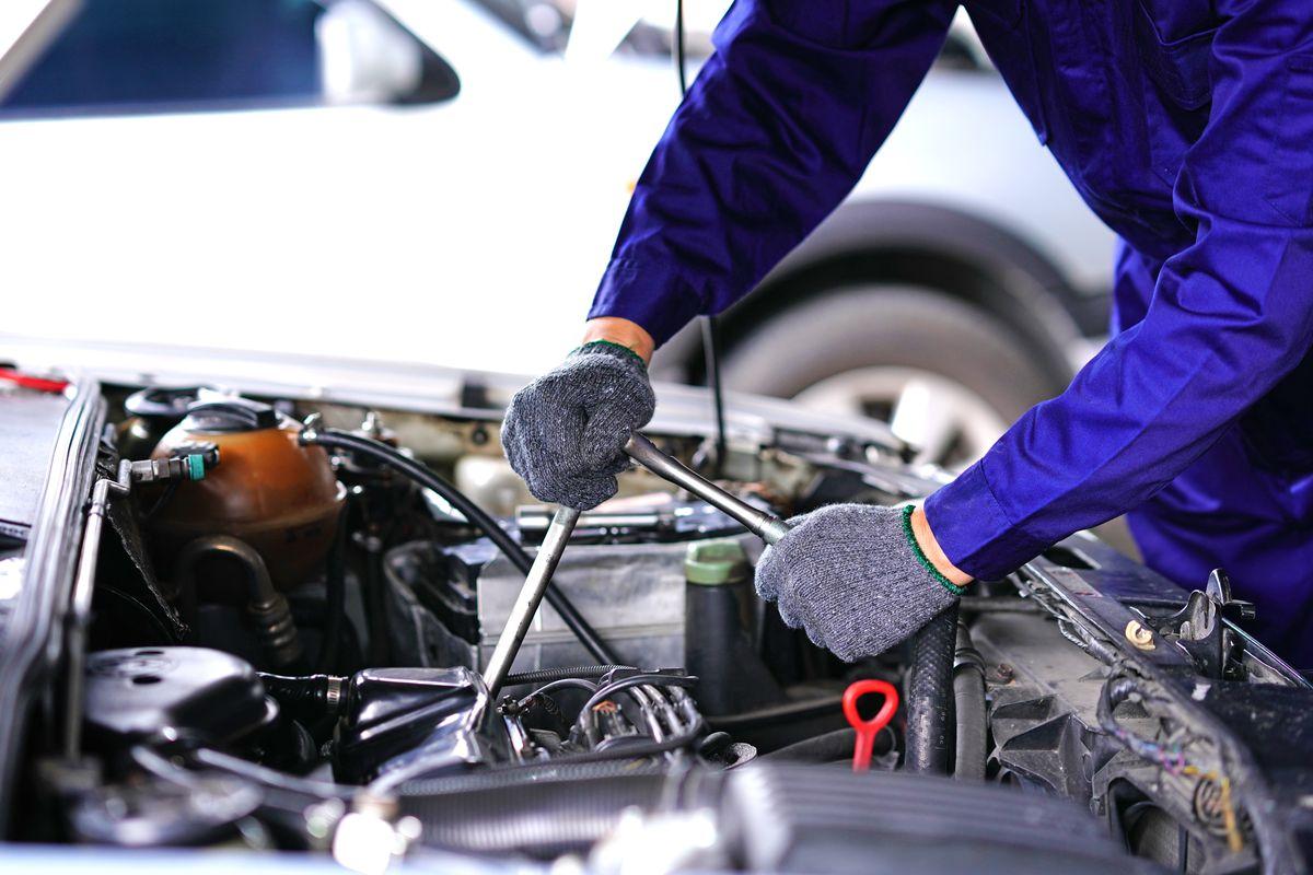 An auto mechanic repairing a car in a garage.