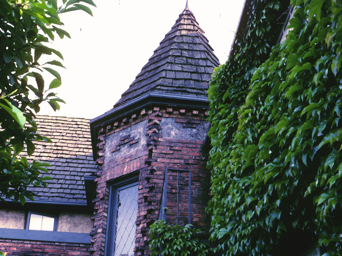 The turret of a brick building. It's nestled inside a corner of the building. The wall to the right is covered in ivy.