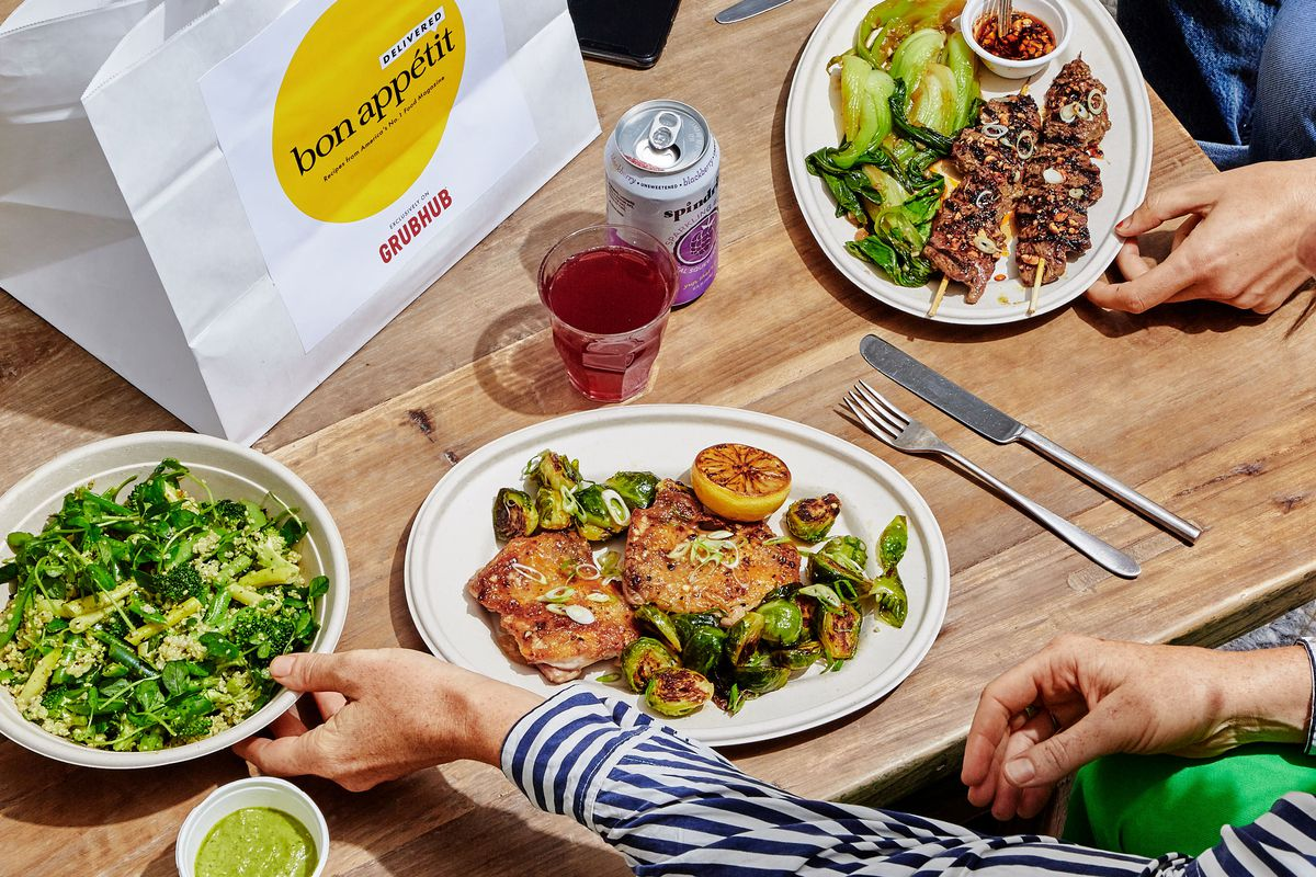 Three plates of food on a wooden table with a bag with the Bon Appetit logo, a drink, a can, and silverware.