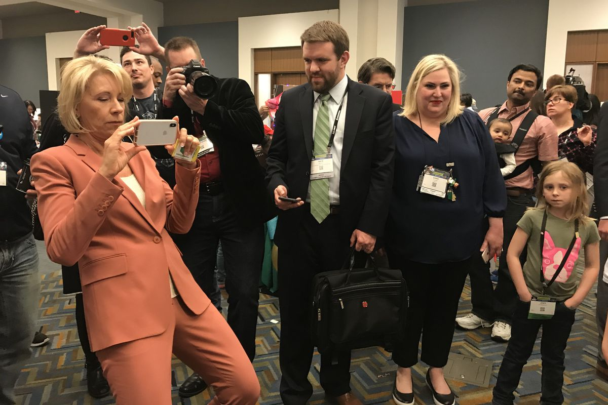 U.S. Education Secretary Betsy DeVos takes pictures on her phone during the FIRST Robotics World Championship, held in Detroit on April 27, 2018.