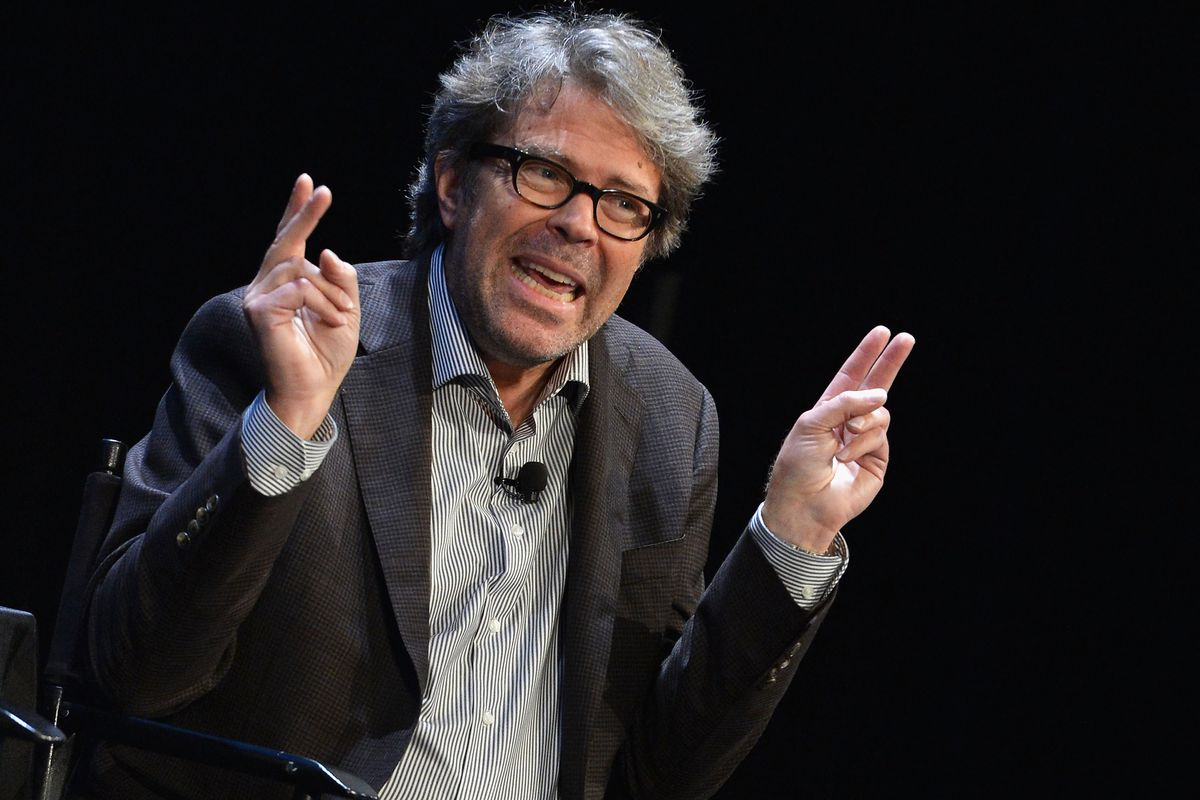 """Jonathan Franzen onstage making """"air quotes"""" with his fingers."""