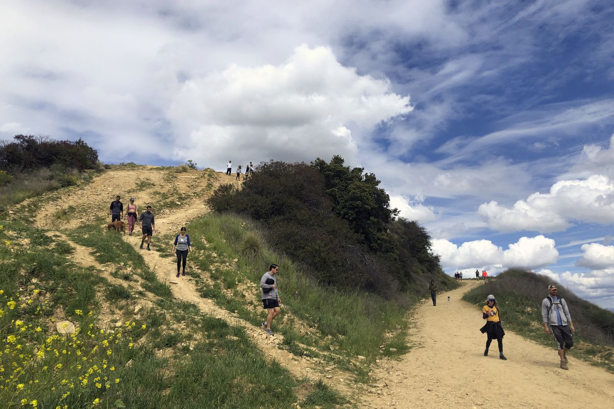 Hikers in colorful clothing converge on two sand-colored trails on a treeless hillside against a bright blue sky.