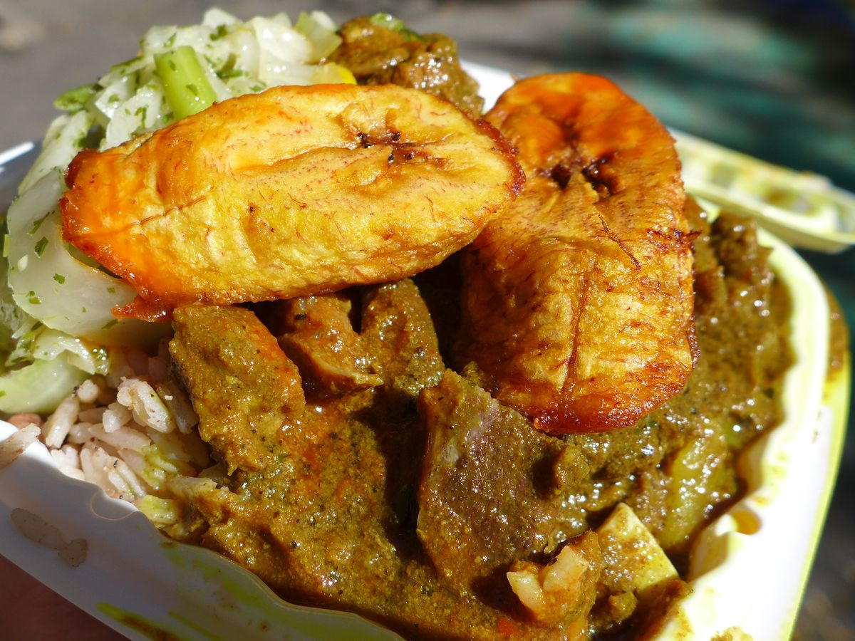Goat curry with plantains in a small Styrofoam container.