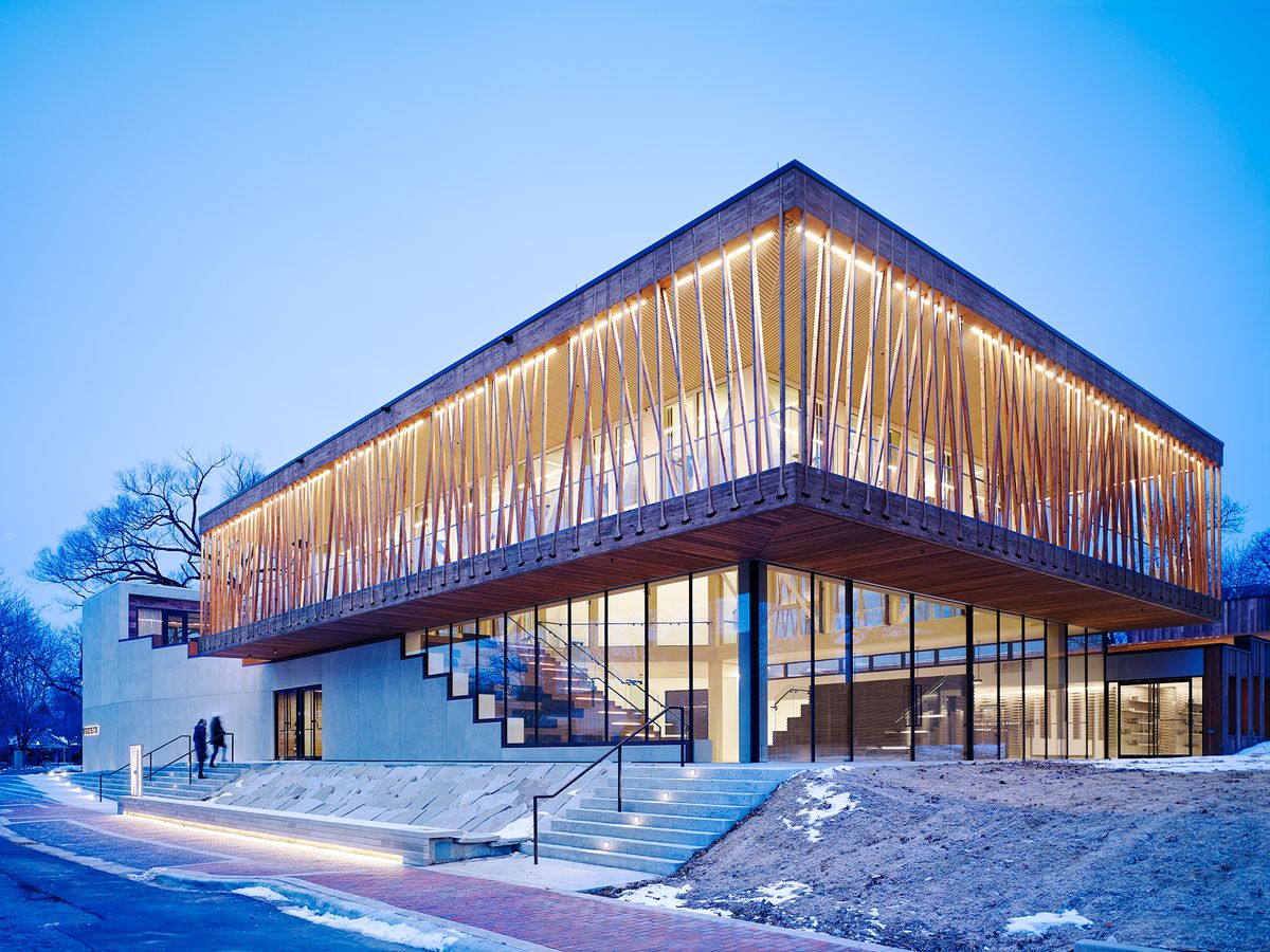 The exterior of the Writers Theatre in Chicago.  The roof is flat and there is a staircase leading to the entrance. The upper level has multiple wooden beams arranged in a latticework design which sit in front of glass windows.