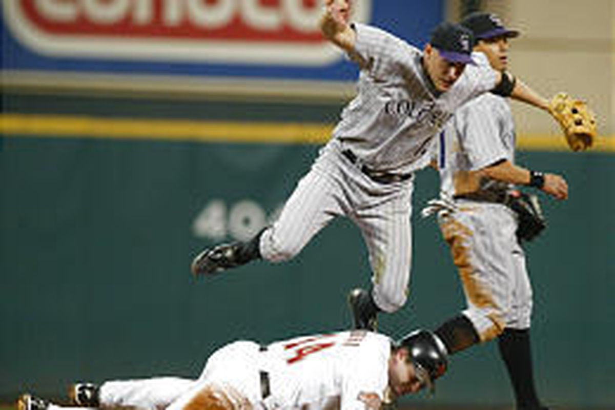 Colorado's Clint Barmes flies over Houston's Morgan Ensberg as he turns a double play on Saturday.