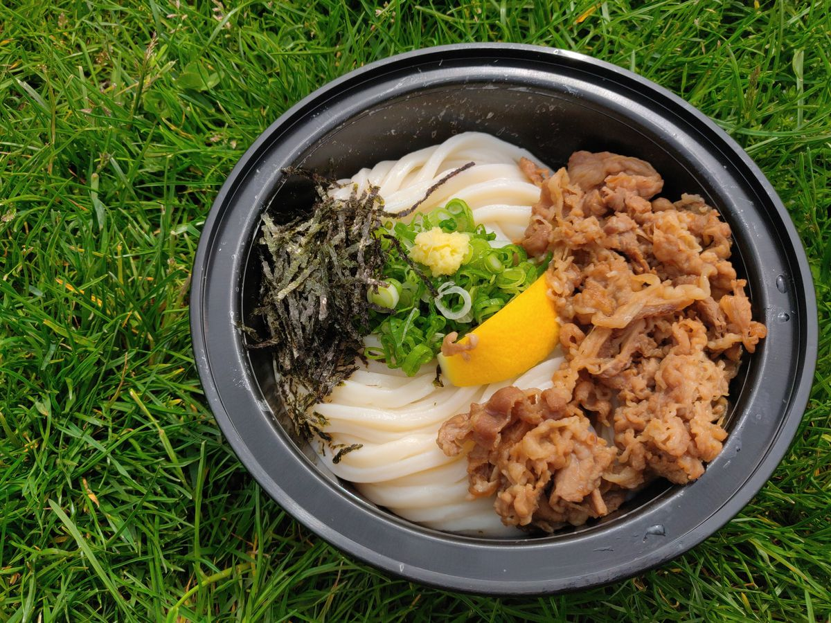 A black plastic takeout bowl is filled with udon and thinly cut beef. It's all topped with a lemon slice, green scallions, and seaweed. The bowl sits on green grass.