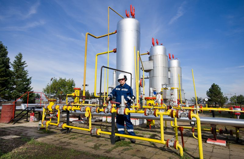A man in work clothes stands amid a curving mass of pipes at a natural gas plant.