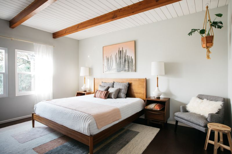 A bedroom with two windows, wooden platform bed, and gray armchair.