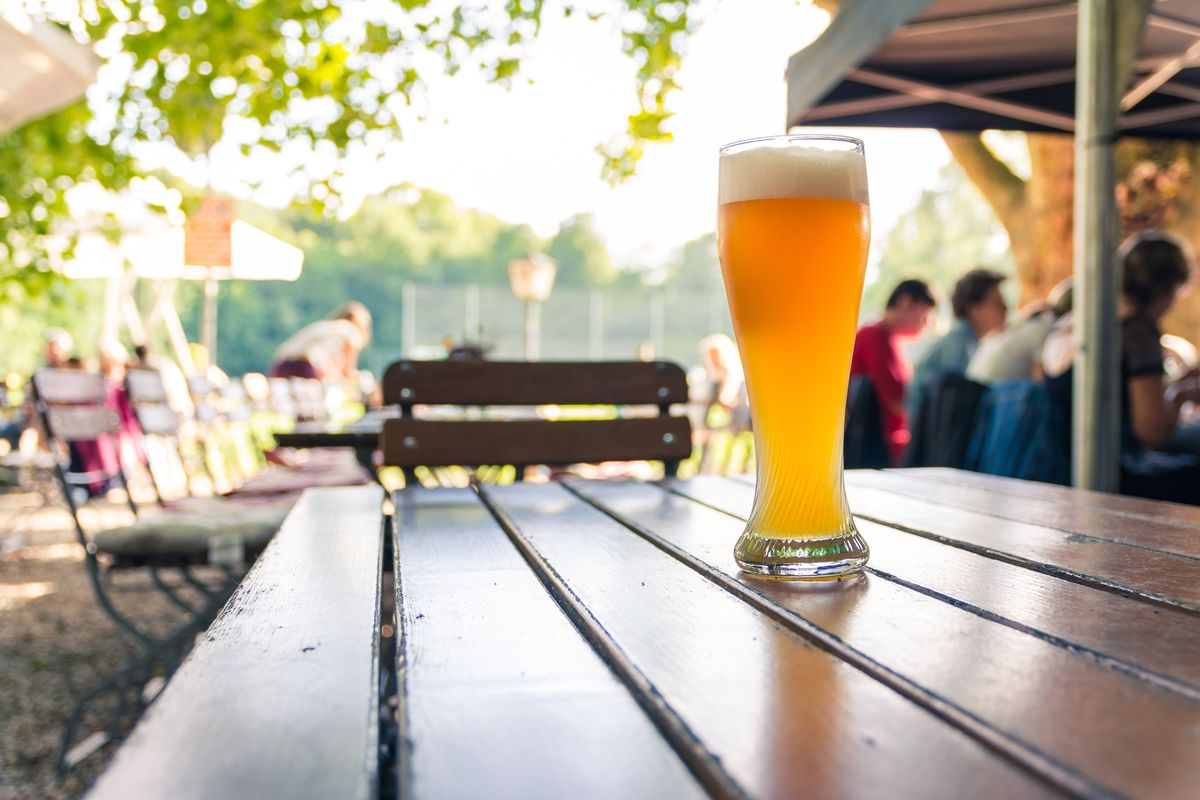 A stock photograph of a glass of beer on an outdoor table in a beer garden