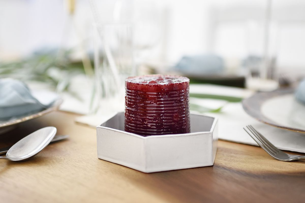 Cranberry sauce, still in the shape of the can, in a dish on a set table.
