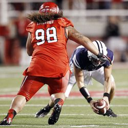 Brigham Young Cougars quarterback Riley Nelson (13) has trouble with the snap as Utah Utes defensive tackle Viliseni Fauonuku (98) pursues in Salt Lake City  Sunday, Sept. 16, 2012.