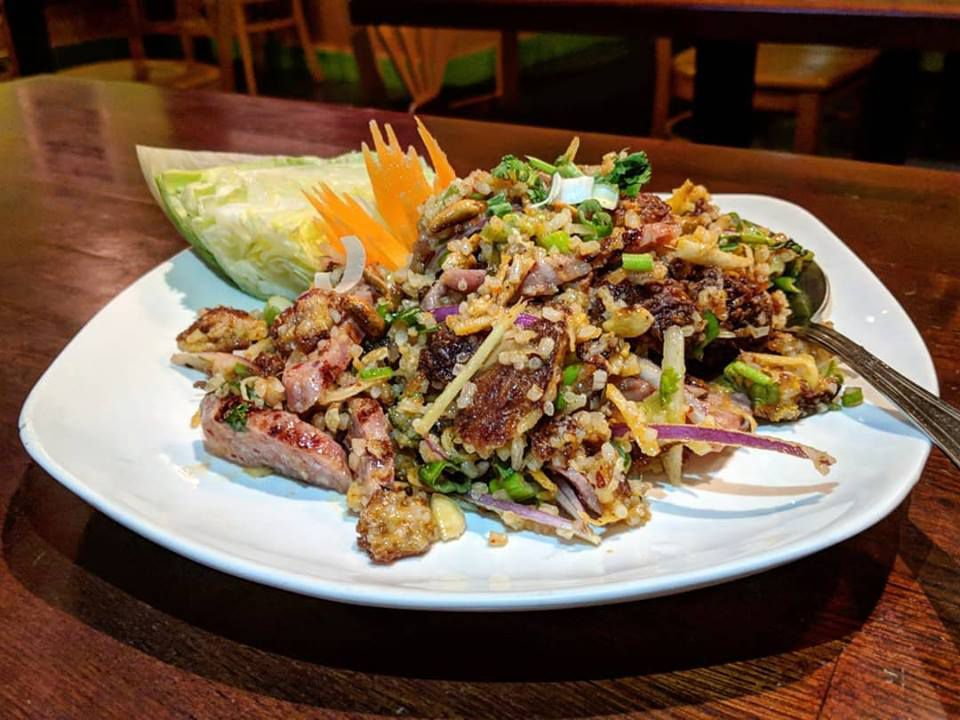 A sausage and crispy rice salad sits on a white plate on a wooden table.