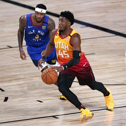 Utah Jazz's Donovan Mitchell (45) drives up the court as Denver Nuggets' Torrey Craig (3) defends during the first half of an NBA basketball first round playoff game Sunday, Aug. 23, 2020, in Lake Buena Vista, Fla.