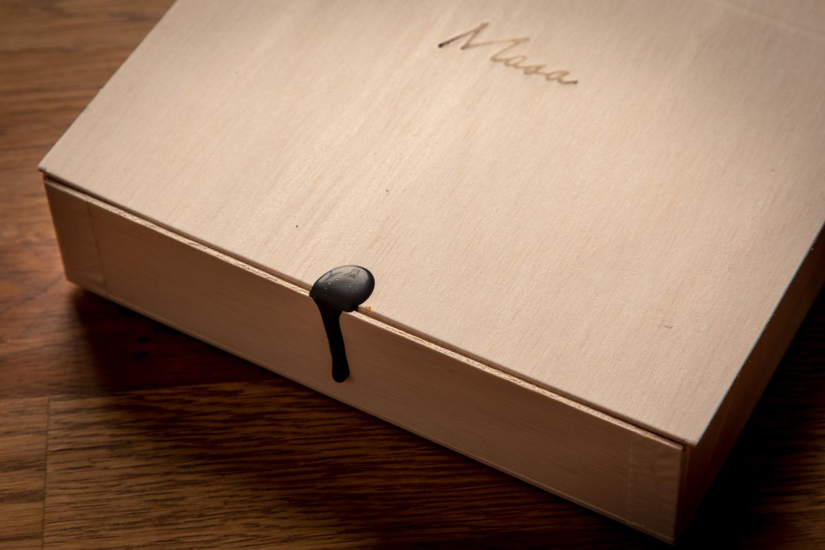 """A wax seal on a wooden box with the word """"Masa"""" on it"""