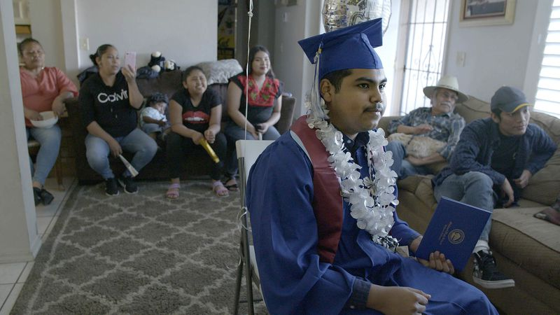 A teenager sits in his graduation gown in his living room, surrounded by family members.