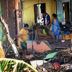 People work to clean up and repair their home in Tacloban, Friday, Nov. 22, 2013.