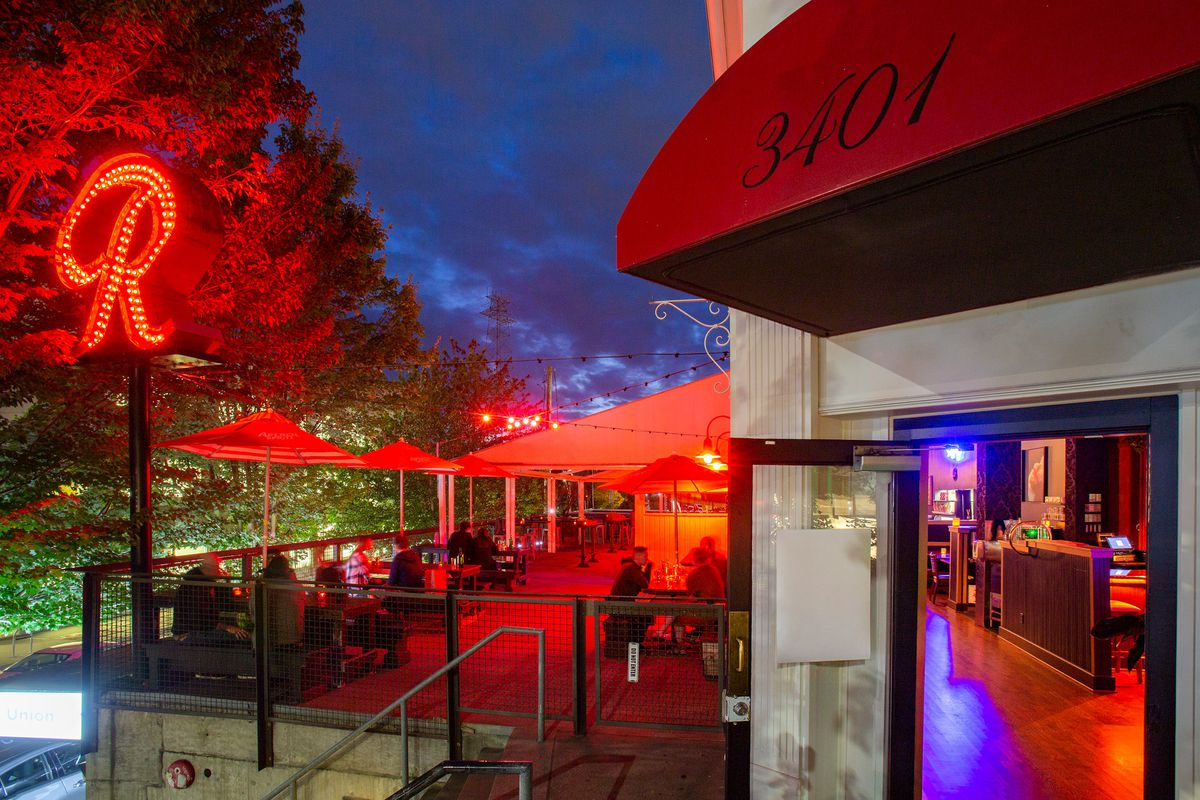 The patio at Dreamland Bar & Diner in Fremont, at night, with a glowing neon Rainier beer sign to the left and a red awning to the right