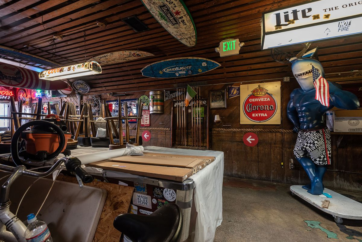 Clutter accumulates inside of a dive bar filled with surfboards and other neon lights.