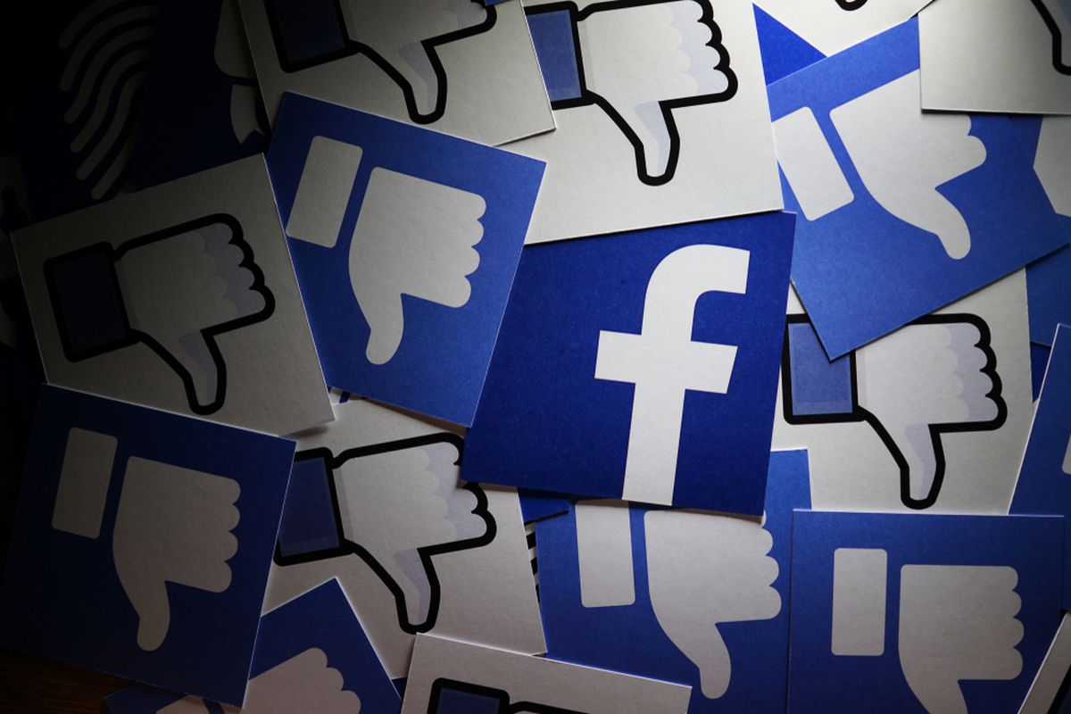 The Facebook logo surrounded by thumbs down icons.