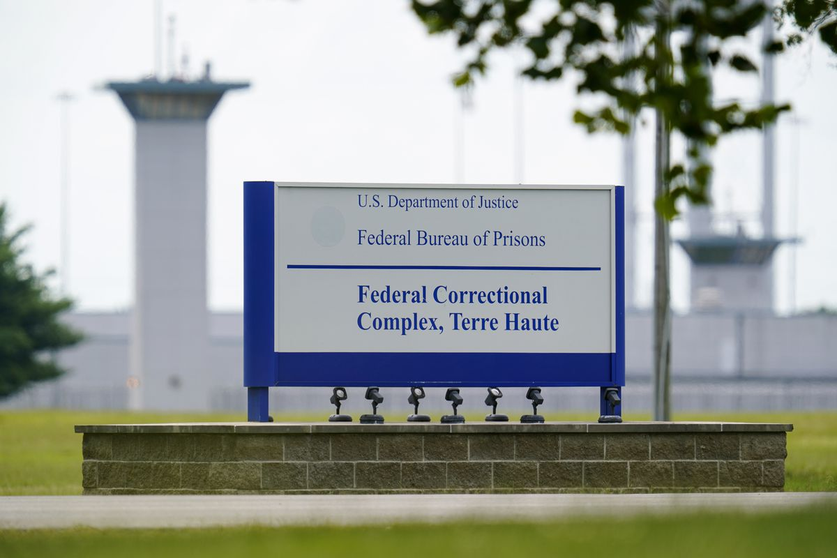 A white, cylindrical prison guard tower rises from a green lawn amid a mass of white buildings. In the foreground is a white sign with blue text, reading: Federal Bureau of Prisons Federal Correctional Complex, Terre Haute.