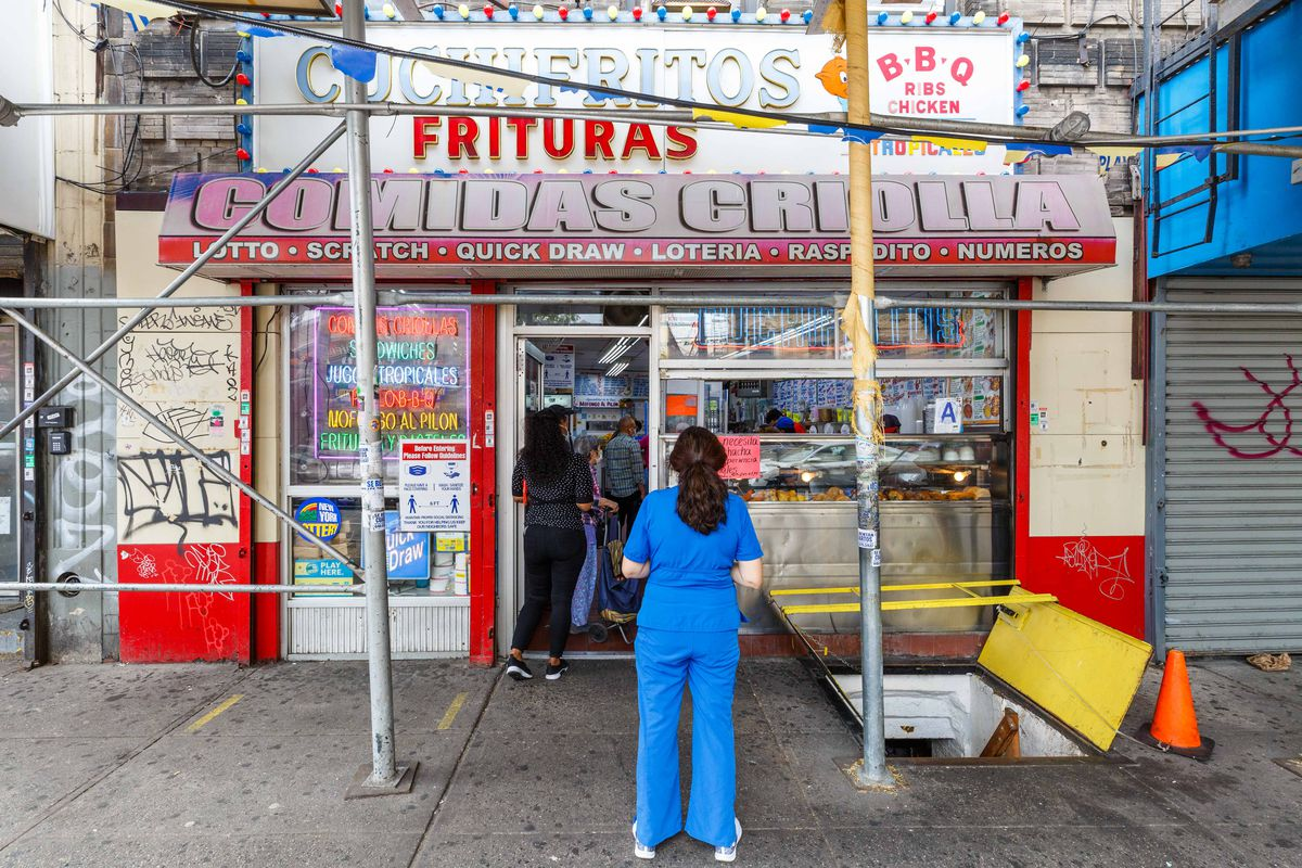 A patron in blue hospital scrubs stands outside 188 Cuchifritos, whose exterior is decorated by neon lights