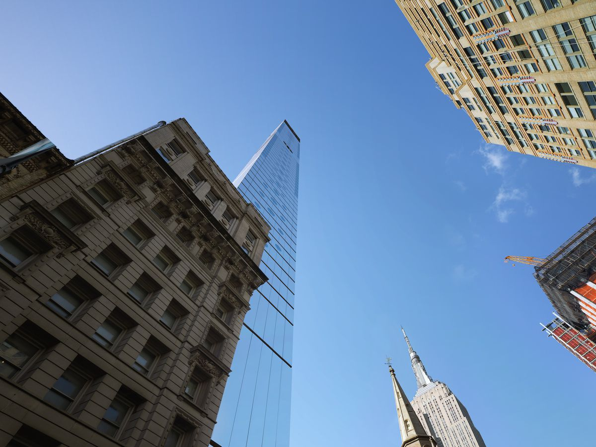 Tall skyscrapers and city buildings against a blue sky.
