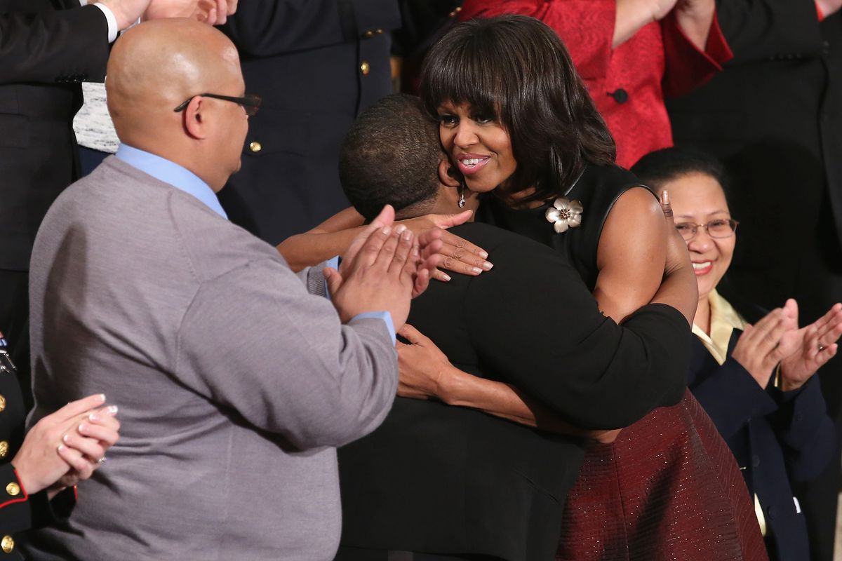 First lady Michelle Obama (R) hugs Cleopatra Cowley-Pendleton (C) and Nathaniel A. Pendleton Sr. (L) of Chicago, Illinois before President Obama's State of the Union speech at the US Capitol February 13, 2013, in Washington, DC.