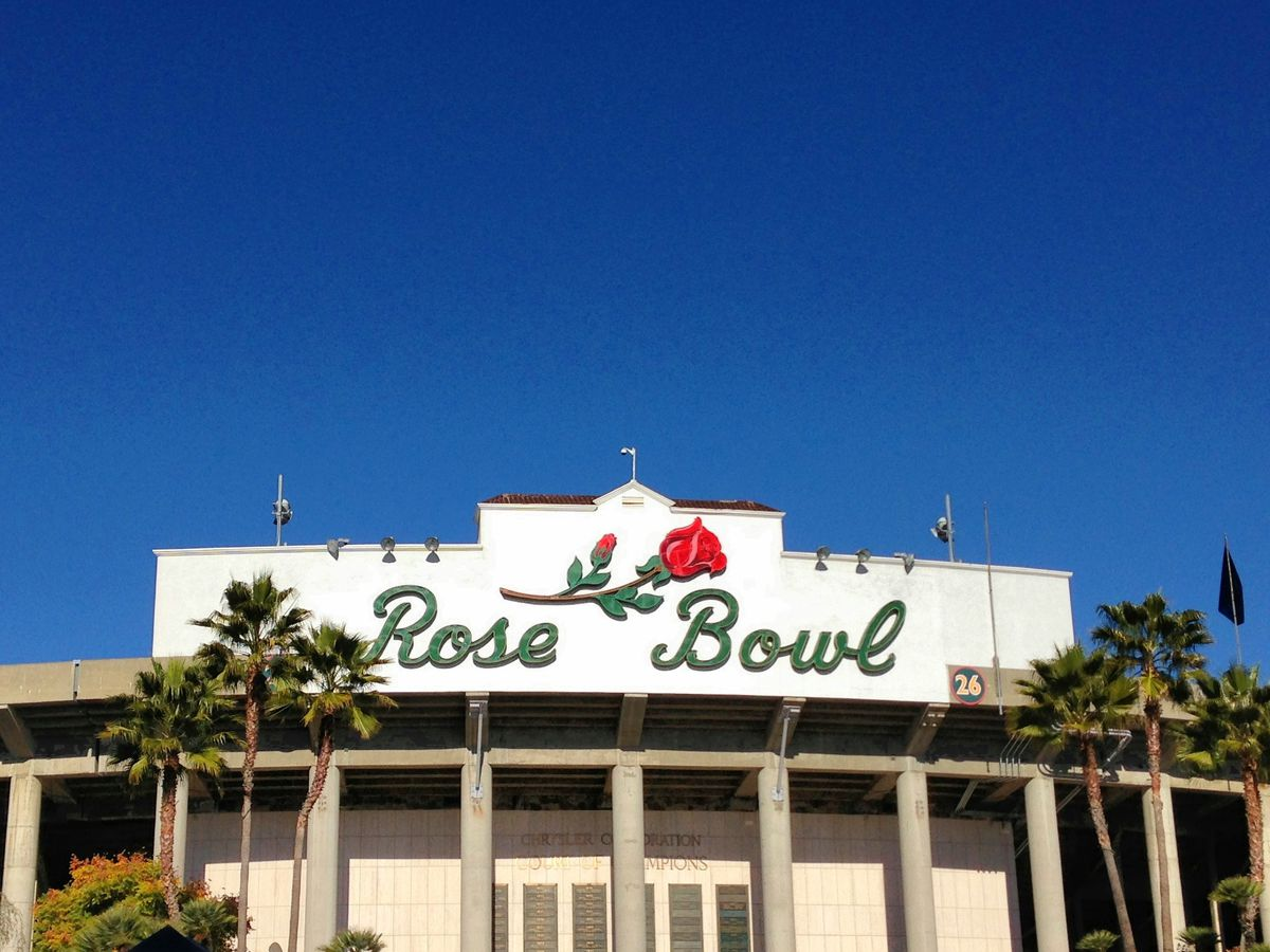 The front of a stadium. A sign above the entrance reads: Rose Bowl.