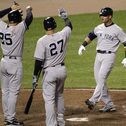 New York Yankees' Nick Swisher, right, meets Mark Teixeira (25) and Raul Ibanez at home plate after driving in Teixeira with a home run in the 10th inning of a baseball game against the Baltimore Orioles in Baltimore, Wednesday, April 11, 2012. New York won 6-4 in 10 innings.